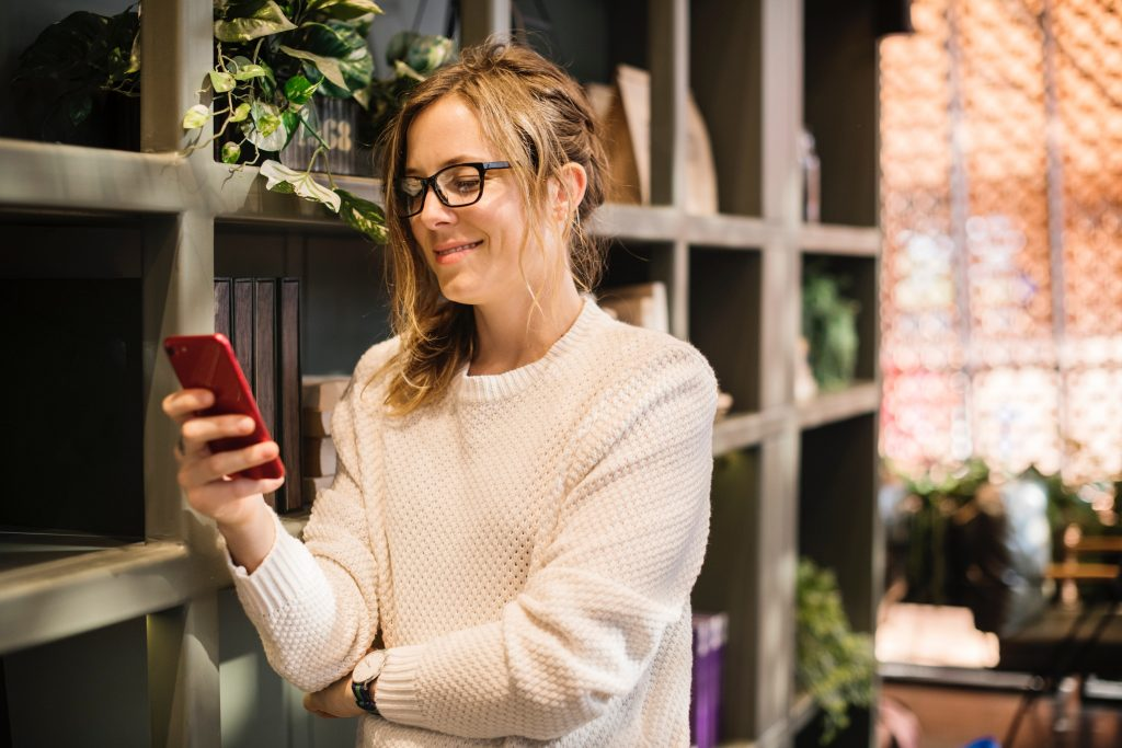 Woman in a white sweater holding a phone and smiling