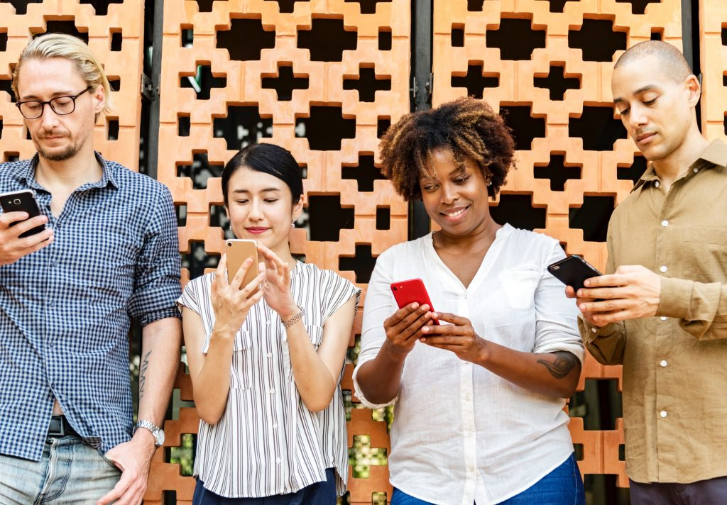 Group of 4 men and women holding phones and looking at them and smiling