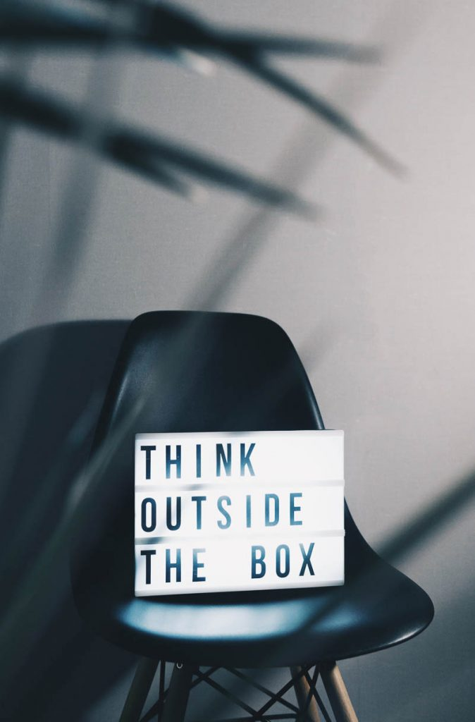 black chair with white sign sitting on it that says think outside the box