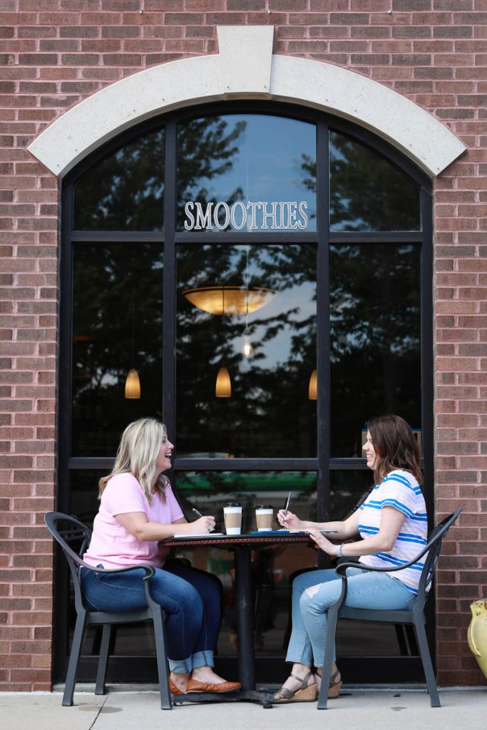 two women enjoying coffee outside of a coffee shop