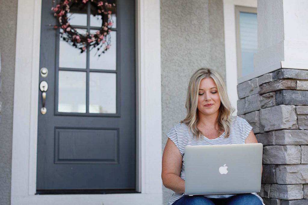 woman sitting on porch working on computer