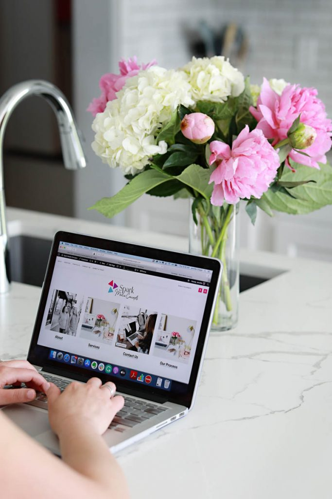 A woman typing on a computer in a kitchen with a bouquet of flowers
