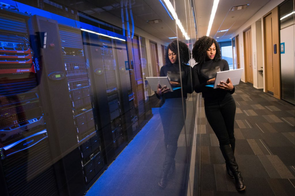 woman with laptop standing next to server room