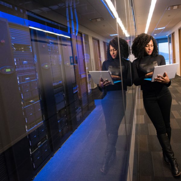 woman holding laptop leaning against computer room