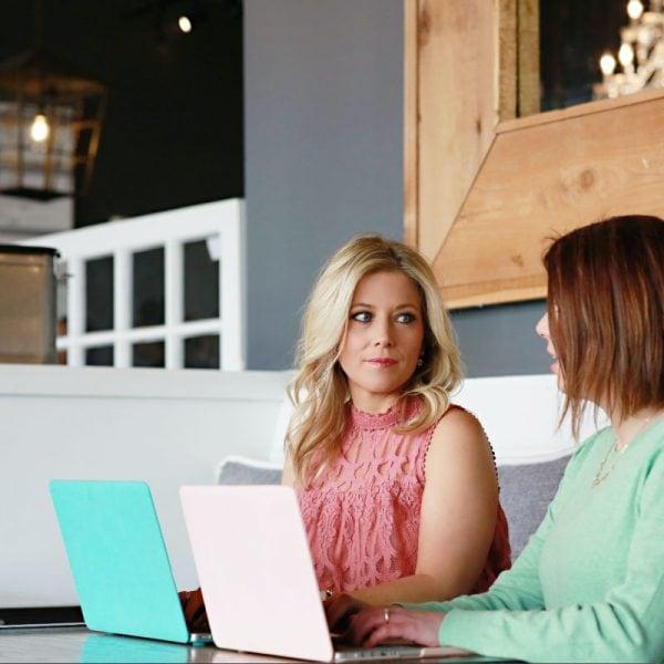 two women working on laptops in a coffee shop