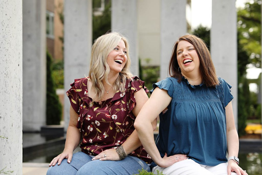 two women laughing together while seated